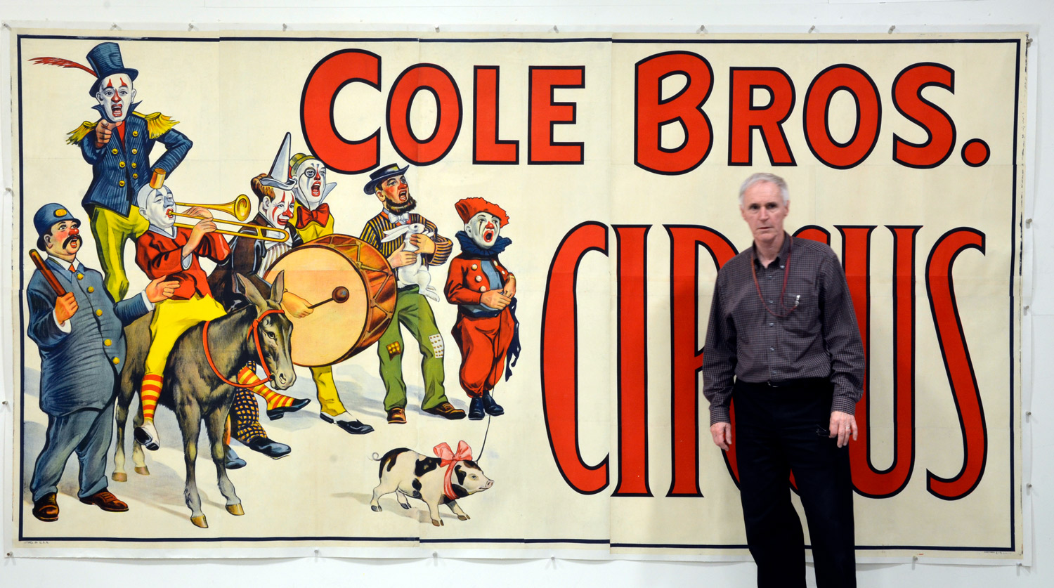 Archivist Ron Levere standing in front of an oversized circus poster in The Ringling Archives