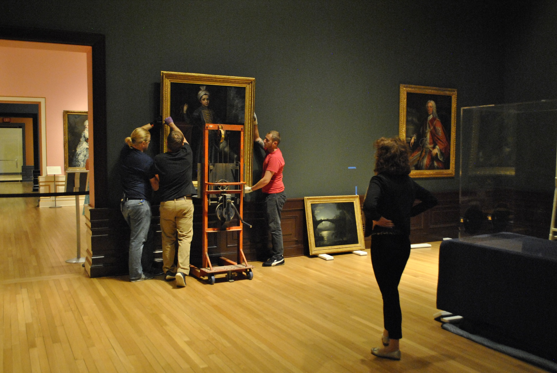 Museum Preparators Hang a painting in a gallery at The Ringling