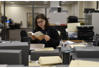Intern in The Ringling Archives reads a book sitting at a table surrounded by files